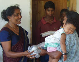 Photo of Mrs. Prem presenting a section of new fishing net to a Sri Lankan Tsunami widow.
